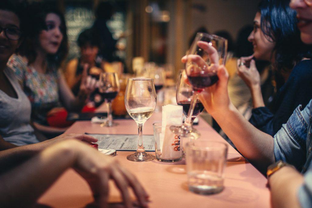 Groupe d'amis qui boivent du vin pendant un repas au restaurant