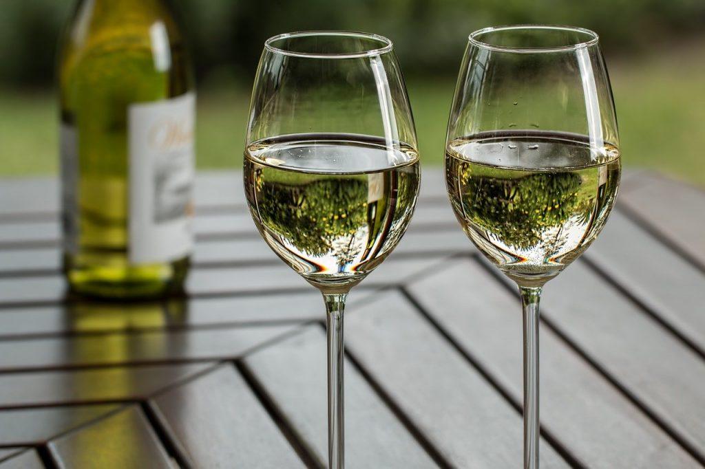 deux verres de vin posés sur une table avec une bouteille de vin blanc en arrière plan
